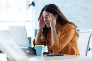 Jeune femme d'affaires avec un mal de tête travaillant avec un ordinateur portable dans un bureau.