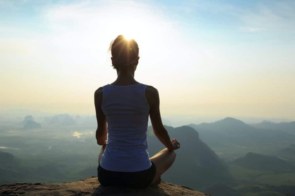 Méditation sur le lever du soleil au bord d'une falaise en haut d'une montagne