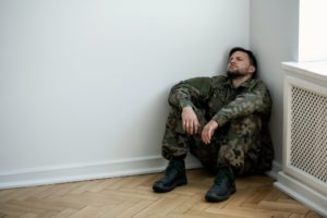 Un militaire en uniforme, déprimé, assis dans le coin d'une salle vide.