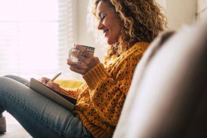 Une jolie femme heureuse à la maison écrit des notes sur un journal intime tout en buvant une tasse de thé et en se relaxant.